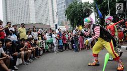 Aksi badut yang tergabung dalam Aku Badut Indonesia menghibur masyarakat saat car free day di Bunderan HI, Jakarta, Minggu (9/12). Aksi tersebut bentuk kampanye positif bertujuan mengajak masyarakat peduli terhadap sesama. (Liputan6.com/Faizal Fanani)