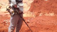 Seorang penambang emas menggunakan detektor logam di sebuah situs penambangan di kota Betare Oya, Kamerun (4/4).  (AFP Photo/Reinnier Kaze)