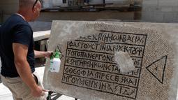 Seorang arkeolog meneliti lantai mosaik berusia 1.500 tahun di Museum Rockefeller, Yerusalem, Rabu (23/8). Prasasti tersebut menyebutkan nama Kaisar Romawi abad ke-6 Justinian dan juga Constantine. (AHMAD GHARABLI/AFP)