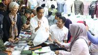 Presiden Jokowi menemani Direktur Pelaksana IMF Christine Lagarde memilih baju koko di salah satu toko Blok A Pasar Tanah Abang, Jakarta, Senin (26/2). Baju koko tersebut dibeli Lagarde sebagai oleh-oleh untuk sang suami. (Liputan6.com/Angga Yuniar)