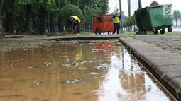 Petugas membersihkan sampah di kawasan Monas, Jakarta, Senin (3/11). Kesigapan petugas kebersihan pasca reuni 212 membuat kawasan tersebut kembali bersih meskipun sehari sebelumnya dipenuhi ratusan ribu orang. (Liputan6.com/Immanuel Antonius)