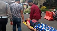 Polisi menggotong salah satu dari empat tahanan kabur dari penjara Polres Malang Kota yang ditembak saat ditangkap di tempat persembunyiannya (Liputan6.com/Zainul Arifin)