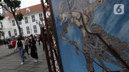Pengunjung berjalan-jalan di kawasan wisata Kota Tua Jakarta, Minggu (4/4/2021). Libur panjang perayaan Paskah 2021 dimasa pemberlakuan PPKM Berskala mikro dimanfaatkan sejumlah warga untuk berwisata di kawasan Kota Tua Jakarta. (Liputan6.com/Helmi Fithriansyah)
