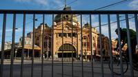 Pesepeda melewati Stasiun Flinders Street yang kosong selama lockdown atau penguncian wilayah di Melbourne, Kamis (6/8/2020). Negara bagian Victoria, hotspot COVID-19 di Australia, melakukan lockdown dan menutup bisnis ritel sebagai upaya mencegah penyebaran virus corona. (AP Photo/Andy Brownbill)