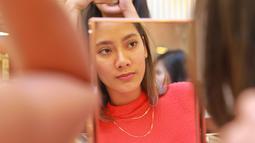 Tara Basro saat sedang memperhatikan wajah cantiknya di depan kaca. Dalam pantulan kaca, Tara sangat memesona jelang acara pembukaan butik 'Tulola Jewelry' dan peluncuran webseries Tulola. (KapanLagi.com/Adrian Utama Putra)