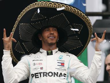 Pembalap Mercedes dari Inggris, Lewis Hamilton mengenakan topi sombrero merayakan keberhasilannya menjuarai balapan GP Meksiko di Autodromo Hermanos Rodriguez, Mexico City (28/10/2019). Kemenangan ini mendekatkan Hamilton ke titel juara dunia F1 2019. (AP Photo/Rebecca Blackwell)