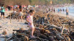 Seorang gadis melintas di atas sampah yang terdampar akibat cuaca buruk di Pantai Kuta, Bali, Jumat (15/2). Sampah bervolume besar kembali menepi di Pantai Kuta, kali ini pesisir pantai berpasir putih itu dipenuhi sampah buah kelapa. (SONNY TUMBELAKA/AFP)