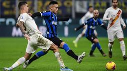 Striker Inter Milan, Lautaro Martinez, berusaha melewati bek AS Roma, Gianluca Mancini, pada laga Serie A Italia di Stadion San Siro, Milan, Jumat (6/12). Kedua klub bermain imbang 0-0. (AFP/Miguel Medina)