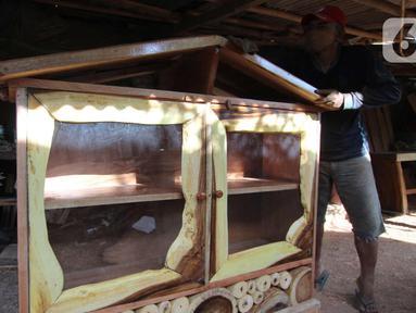 Perajin menyelesaikan pembuatan kursi dari kayu bekas di Pinang, Kota Tangerang, Banten, Minggu (28/3/2021). Furnitur berbahan dasar kayu bekas tersebut dijual dari harga Rp50.000 hingga lima juta rupiah dan dipasarkan hingga ke Sumatera dan Kalimantan. (Liputan6.com/Angga Yuniar)