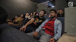 Relawan bisik menjelaskan alur cerita kepada penyandang tunanetra saat menyaksikan film di Bioskop Bisik di Pavilliun 28, Jakarta, Minggu (14/1). Hal ini membuat menonton bioskop bukan menjadi hal mustahil lagi bagi tunanetra. (Liputan6.com/Faizal Fanani)