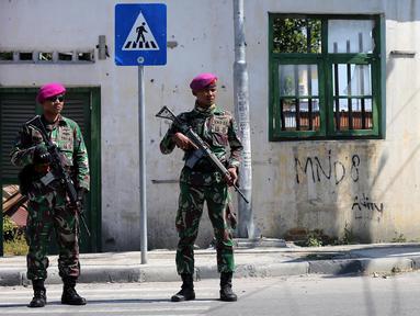 Dua prajurit Marinir TNI Angkatan Laut berjaga di perempatan lampu merah kota Palu pascagempa dan tsunami di Palu, Sulawesi Tengah, Jumat (5/10). TNI kembali mengirimkan pasukan untuk memulihkan Kota Palu. (Liputan6.com/Fery Pradolo)