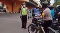 Seorang personel Bhabinkamtibmas berusaha menerobos penyekatan PPKM level 4 Pekanbaru. (Liputan6.com/M Syukur)