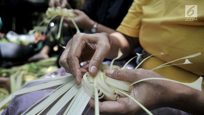 Umat Hindu bersama-sama membuat sajen (Ngayah) di Pura Aditya Jaya, Jakarta, Senin (4/3). Ngayah merupakan tradisi yang dilakukan gotong-royong oleh kaum perempuan Hindu dalam membuat sajen untuk persiapan sembahyang  Nyepi. (merdeka.com/Iqbal S. Nugroho)