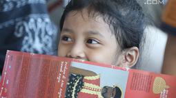 Seorang anak tertawa saat menyaksikan aksi pementasan cerita sejarah pertempuran pasukan Mataram di Museum Nasional Indonesia, Jakarta, Minggu (29/4). Dongeng tersebut berkisah penyerangan Sultan Agung ke Batavia. (Liputan6.com/Helmi Fithriansyah)