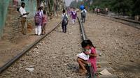Seorang gadis muda membaca buku sambil duduk di rel kereta api di New Delhi, India, Selasa (16/10). Sekitar 800 juta warga India hidup dalam kemiskinan. (AP Photo/Altaf Qadri)