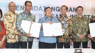 Menteri PPN/Kepala Bappenas Bambang Brodjonegoro (tengah) menunjukkan nota kerja sama investasi di Bali, Sabtu (13/10). Bappenas berhasil memfasilitasi kerja sama investasi dengan perkiraan total nilai Rp 47 triliun. (Liputan6.com/Angga Yuniar)