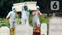 Petugas membawa peti berisi jenazah yang akan dimakamkan dengan protokol COVID-19 di TPU Bambu Apus, Jakarta, Jumat (22/1/2021). Sejak dibuka Kamis (21/1) kemarin hingga hari ini, tercatat sekitar 35 jenazah dimakamkan dengan protokol COVID-19 di TPU Bambu Apus. (Liputan6.com/Helmi Fithriansyah)