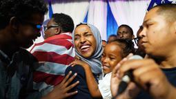 Ilhan Omar menggendong anaknya saat merayakan kemenangan pemilihan Distrik Kongres ke-5 di Minneapolis, AS, Selasa (14/8). Omar mencetak sejarah dengan memenangi putaran pertama pemilihan Distrik Kongres ke-5. (Mark Vancleave/Star Tribune via AP)