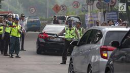 Petugas polisi lalu lintas memberhentikan kendaraan saat pemberlakuan sistem ganjil genap di pintu masuk Gardu Tol Cibubur 2, Jakarta, Senin (16/4). Aturan ganjil genap ini diujicobakan di Gerbang Tol pada  Senin 16 April 2018.(Liputan6.com/Faizal Fanani)