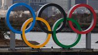 Pekerja berjalan di kapal tongkang yang membawa Cincin Olimpiade di Distrik Odaiba, Tokyo, Jepang, Jumat (17/1/2020). Cincin Olimpiade dengan tinggi 15,3 meter dan panjang 32,6 meter tersebut akan berada di sana hingga Olimpiade 2020 berakhir. (AP Photo/Jae C. Hong)