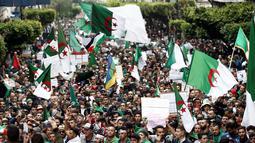 Demonstran memegang bendera dan spanduk saat berunjuk rasa di Aljir, Aljazair, Jumat (19/4). Demonstran kembali turun ke jalan-jalan untuk mendesak perubahan demokrasi besar-besaran melampaui pengunduran diri mantan presiden Abdelaziz Bouteflika. (REUTERS/Ramzi Boudina)