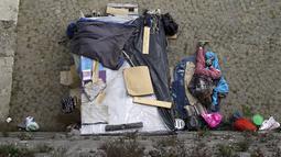 Seorang tunawisma tertidur di samping tendanya di kawasan permukiman kumuh bawah jembatan di Sungai Tiber, Roma, Italia (13/4). Kondisi tempat tinggal para tunawisma tersebut tak jauh beda dengan di Jakarta. (REUTERS / Max Rossi)