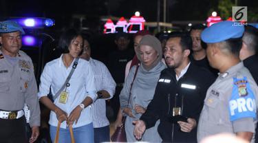 Aktivis Ratna Sarumpaet (tengah) saat dibawa menuju ruang Direktorat Reserse Kriminal Umum Polda Metro Jaya, Jakarta, Kamis (4/10). Ratna Sarumpaet dibawa polisi dari Bandara Soekarno-Hatta, Kamis (4/10) malam. (Liputan6.com/Helmi Fithriansyah)