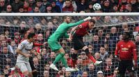 Kiper Man United, David de Gea melakukan penyelamatan pada laga lanjutan Premier League yang berlangsung di Stadion Old Trafford, Minggu (14/4). Man United menang 2-1 atas West Ham. (AFP/Paul Ellis)
