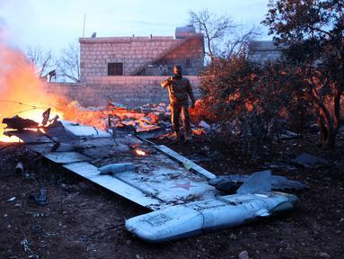 Seorang militan Suriah mengambil gambar jet tempur Sukhoi-25 milik Rusia yang jatuh di provinsi Idlib, Suriah (3/2). Menurut laporan lembaga Observasi HAM Suriah, jet tempur Rusia itu ditembak jatuh pada Sabtu sore. (AFP/Omar Haj Kadour)