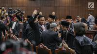 Ketua Tim Hukum Jokowi-Ma'ruf Amin, Yusril Ihza Mahendra melambaikan tangan kepada wartawan usai putusan MK di Gedung MK, Jakarta, Kamis (27/6/2019). MK menolak seluruh gugatan hasil Pilpres 2019 yang diajukan Prabowo-Sandiaga Uno yang disepakati 9 hakim konstitusi. (Liputan6.com/Faizal Fanani)