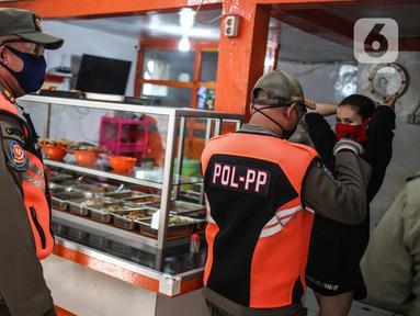 Petugas Satpol PP menertibkan warung makan yang melanggar aturan pembatasan sosial berskala besar (PSBB) di kebon kacang, Jakarta, Senin (1/6/2020). Pelanggaran berupa menerima pelanggan yang makan di warung ditertibkan oleh petugas untuk mencegah penyebaran COVID-19. (Liputan6.com/Faizal Fanani)