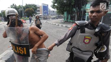 Anggota Sabhara Polri menangkap pengunjuk rasa saat bentrok  dengan massa aksi 22 Mei sebelum terjadi pembakaran bis milik Brimob di kawasan Tanah Abang,  Jakarta, Rabu (22/5/2019). (merdeka.com/Arie Basuki)