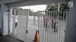 Warga yang berolahraga mengamati kerusakan pintu masuk zona 9 Stadion Utama Gelora Bung Karno, Jakarta, Minggu (18/2). Ratusan Jakmania yang tak memiliki tiket final Piala Presiden 2018 memaksa masuk stadion hingga pintu jebol (Liputan6.com/Faizal Fanani)