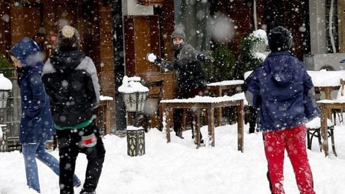 Pemuda Iran bermain salju (AFP/ATTA KENARE).