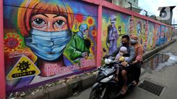 Pengendara sepeda motor melintasi mural bertema COVID-19 di kawasan Tanah Tinggi, Tangerang, Banten, Rabu (20/1/2020). Kegiatan ini dalam rangka mensosialisasikan bahaya penyebaran COVID-19 kepada warga pengguna jalan umum. (merdeka.com/Arie Basuki)