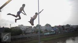 Anak-anak melompat dari atas jembatan dan berenang di aliran kali besar Banjir Kanal Barat, Jakarta, Sabtu (11/3). Minimnya pengawasan orang tua membuat mereka bermain di tempat berbahaya dan mengancam keselamatan. (Liputan6.com/Faizal Fanani)