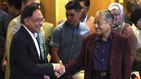 Perdana Menteri Malaysia Mahathir Mohamad (kanan) berjabat tangan dengan Anwar Ibrahim di Putrajaya, Malaysia, Sabtu (22/2/2020). Sebelumnya, Mahathir telah berjanji akan menyerahkan jabatannya kepada Anwar Ibrahim. (AP Photo/Vincent Thian)