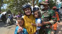 Anggota TNI mengavakuasi seorang wanita beserta kedua orang anak saat terjadi gempa susulan di Tanjung pulau Lombok, NTB, Kamis (9/8).Gempa susulan terjadi kembali dengan kekuatan 6,2 skala richter dikawasan tersebut.(AFP/ ADEK BERRY)
