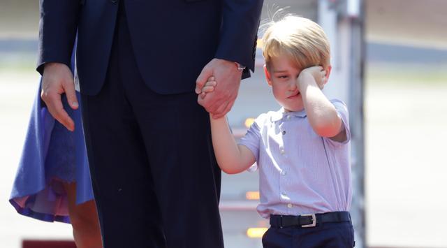 Pangeran George mengusap matanya sambil menggenggam tangan sang ayah, Pangeran William setibanya di Bandara Tegel, Berlin, Rabu (19/7). George ikut dalam tur keluarga kerajaan Inggris bersama Pangeran William dan Kate Middleton. (Kay Nietfeld/dpa via AP)