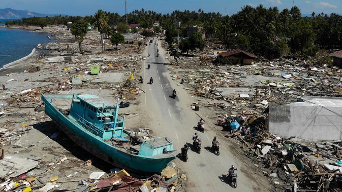 Pengendara sepeda motor melewati perahu dan rerntuhan bangunan usai gempa dan tsunami melanda Palu, Sulawesi Tengah, Senin (1/10). Pihak berwenang tengah menyiapkan kuburan massal untuk memakamkan ratusan korban tewas. (JEWEL SAMAD/AFP)