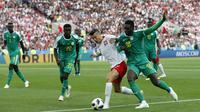 Striker Polandia, Robert Lewandowski, berebut bola  dengan gelandang Senegal, Ismaila Sarr, pada laga Piala Dunia di Stadion Spartak, Selasa (19/6/2018). Senegal menang 2-1 atas Polandia. (AP/Darko Vojinovic)