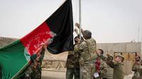 Tentara AS dan Tentara Nasional Afghanistan (ANA) mengibarkan bendera nasional Afghanistan selama upacara penyerahan di Kamp Antonik di provinsi Helmand. (Foto: AFP)