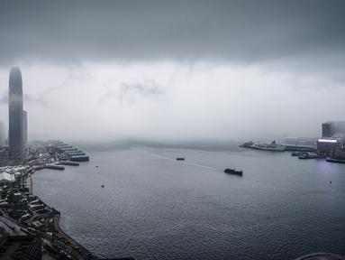Pemandangan gedung IFC (International Finance Center) menjulang di atas dermaga Central saat badai awan terjadi sebelum hujan lebat di atas Pelabuhan Victoria Hong Kong (6/3). (AFP Photo/Anthony Wallace)