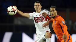 Bek Belanda, Virgil Van Dijk, berebut bola dengan striker Belarusia, Nikolai Signevich, pada laga kualifikasi Piala Dunia 2018 di Stadion Borisov Arena, Borisov, Sabtu (7/10/2017). Belarusia kalah 1-3 dari Belanda. (AP/Sergei Grits)