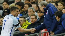 Pemain Inggris, James Milner berjabat tangan dengan pelatih Roy Hodgson saat digantikan Dele Alli pada laga persahabatan di Stadion Wembley, London, Rabu (30/3/2016) dini hari WIB. Belanda menang 2-1. (Reuters/Darren Staples)