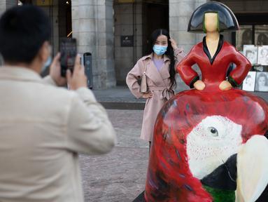 Seorang wisatawan berfoto dengan patung yang terinspirasi dari lukisan Las Meninas di Madrid, ibu kota Spanyol, pada 18 Oktober 2020. Pameran Galeri Meninas Madrid 2020 dimulai di Madrid pada 15 Oktober hingga 15 Desember 2020. (Xinhua/Meng Dingbo)