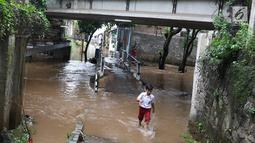 Seorang anak melintasi banjir yang menggenangi kawasan Cilandak Timur, Jakarta Selatan, Selasa (22/1). Hujan deras yang mengguyur Jakarta dan sekitarnya sejak pagi menyebabkan banjir di sejumlah sudut Ibu Kota. (Liputan6.com/Immanuel Antonius)