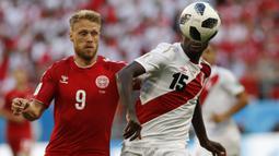 Bek Peru, Christian Ramos, berebut bola dengan striker Denmark, Nicolai Jorgensen, pada laga Grup C Piala Dunia di Mordovia Arena, Saransk, Sabtu (16/6/2018). Denmark menang 1-0 atas Peru. (AP/Efrem Lukatsky)
