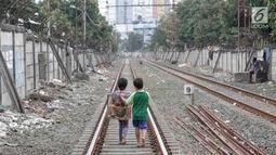 Dua anak berjalan usai bermain di sekitar rel kereta api di kawasan Pademangan, Jakarta, Kamis (8/11). Kurangnya lahan bermain menyebabkan anak-anak tersebut bermain di tempat yang tidak semestinya dan membahayakan. (Liputan6.com/Immanuel Antonius)