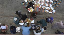 Relawan mengatur makanan untuk warga saat berbuka puasa bersama selama bulan suci Ramadan di Karachi, Pakistan, Selasa (12/5/2020). Warga berbuka puasa bersama setelah pemerintah melonggarkan lockdown terkait pandemi virus corona COVID-19. (AP Photo/Fareed Khan)